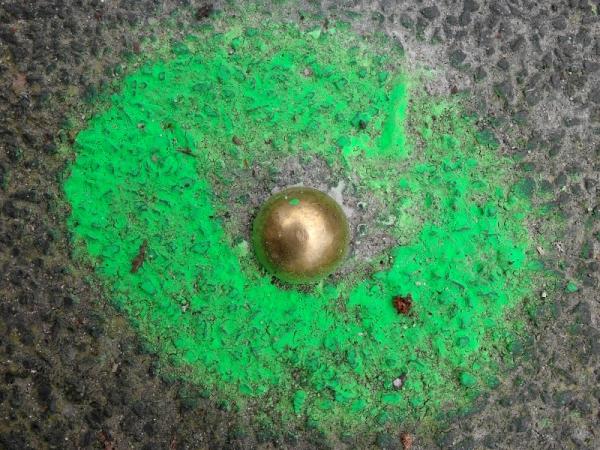 grün markierter Nagel im Asphalt
