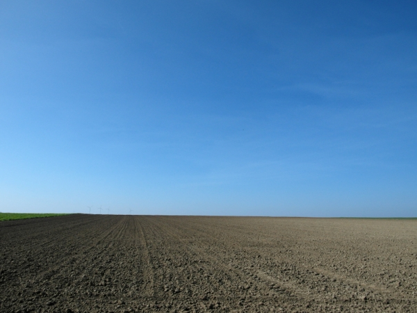 gepflügtes Feld, Windräder, Himmel